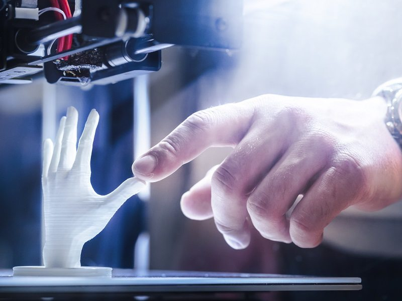 Person's hand touching the thumb of a printed hand.