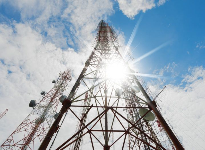 Telecommunication towers including radio microwave and television antenna system with cloudy blue sky and sun rays beaming.