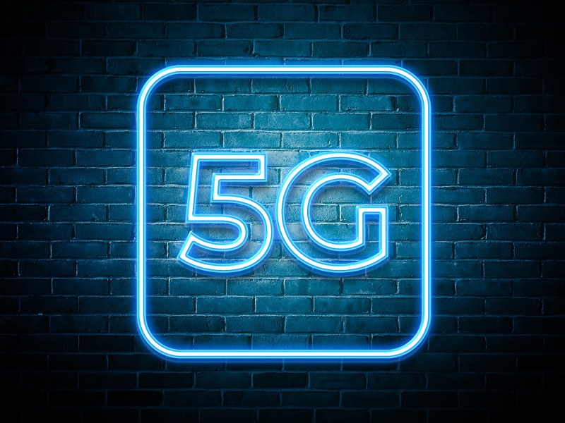 Neon blue 5G sign switched on against a brick wall.