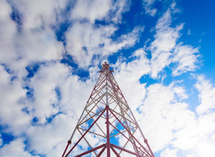 Image of a red telecoms mast under a blue cloudy sky.