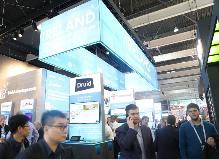 An exhibition stand amid people gathered at Mobile World Congress. A large blue lightbox reads 'Ireland' in white letters.