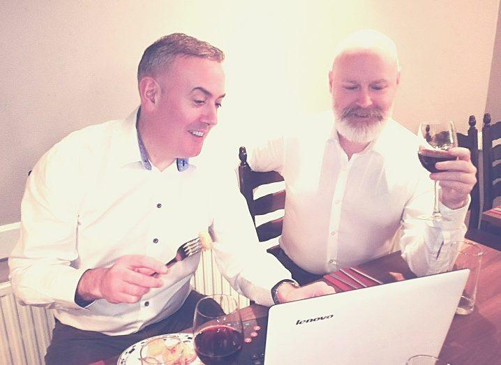 Two men in white shirts eat dinner and drink wine while looking at a computer.