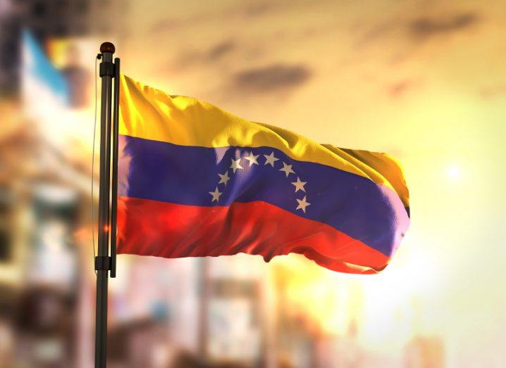 View of the flag of Venezuela flowing against a city-blurred background at sunrise.