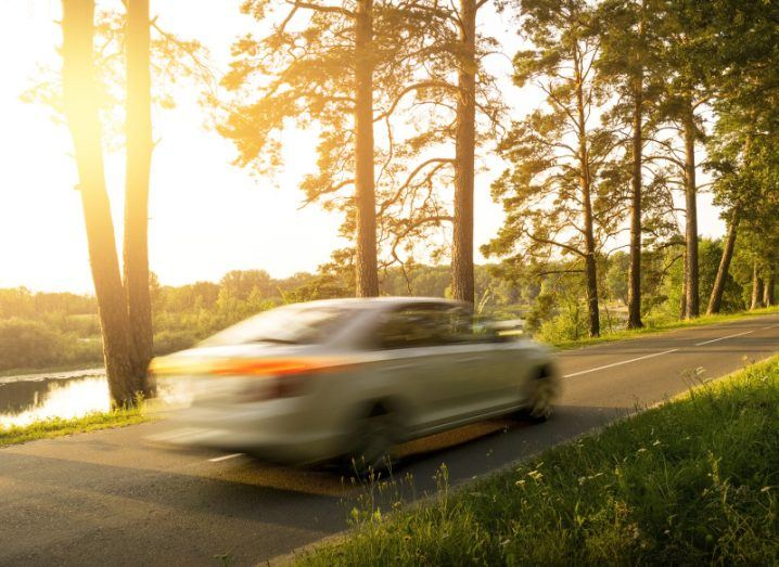 A car whizzes down a lakeside road on a sunny day, creating a motion blur effect.