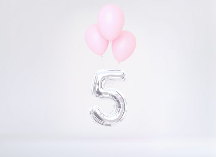 A silver balloon shaped like the number five floats beneath three pink balloons on a white background.