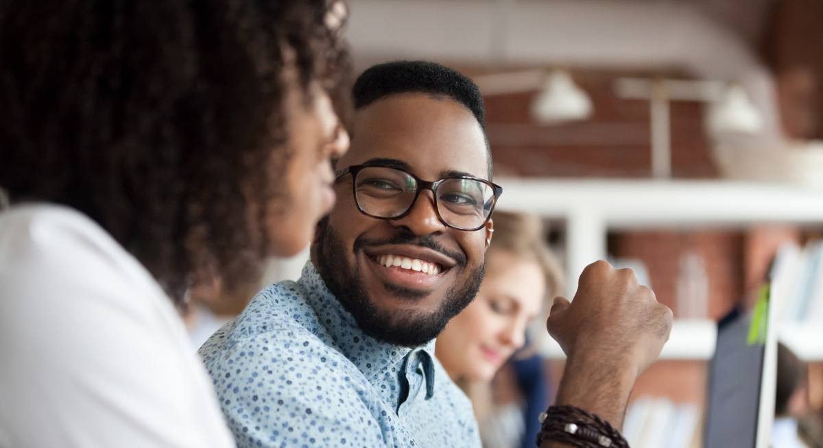 View of a young smiling man wearing thick-rimmed glasses looking at his co-worker.