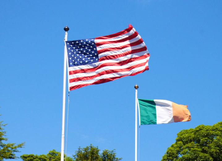 An American flag and an Irish flag blowing in the breeze against a blue sky, representing a US-Ireland research partnership.