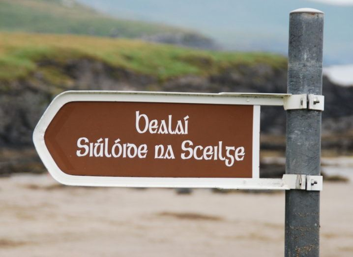 A signpost on a rocky beach reads 'Bealaí Siúlóide na Sceilge' in old Irish writing.