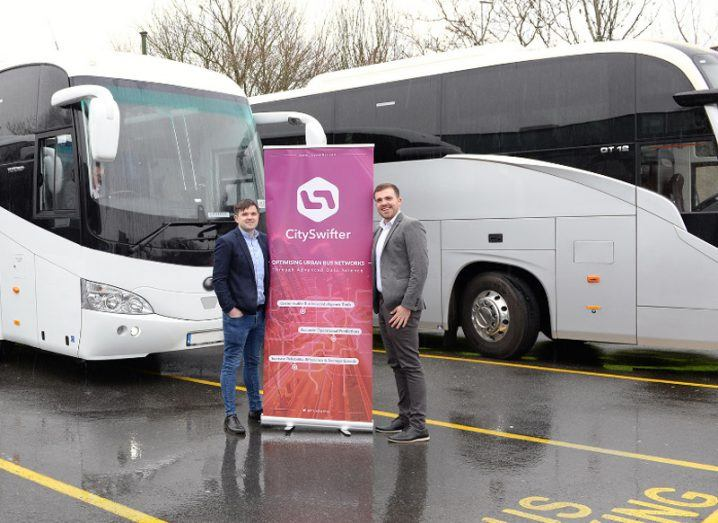Two men hold a pink pop-up sign that reads CitySwifter in front of large buses.