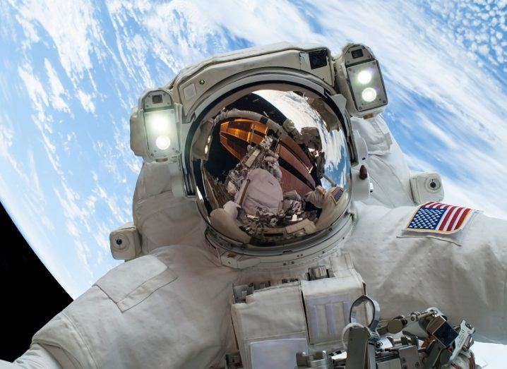 Astronaut facing the camera in a spacesuit with the Earth behind them.