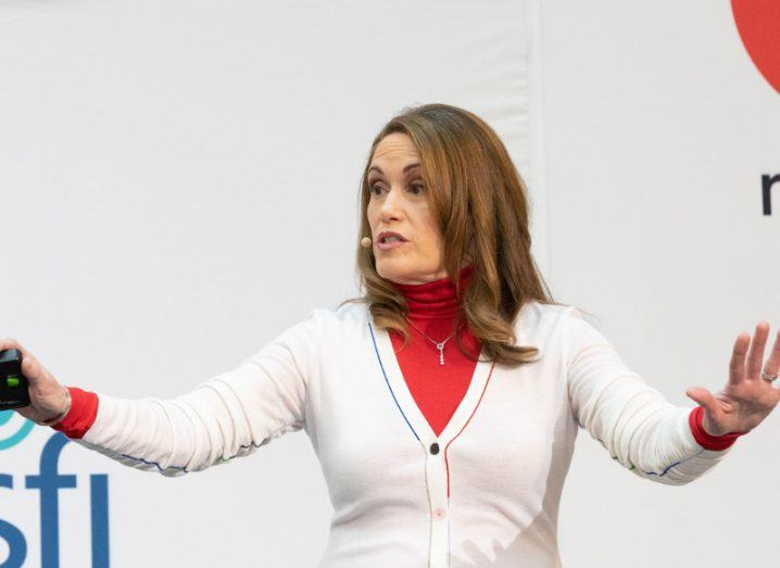 Woman with brown hair wearing a white cardigan and red polo neck gestures while making a presentation.