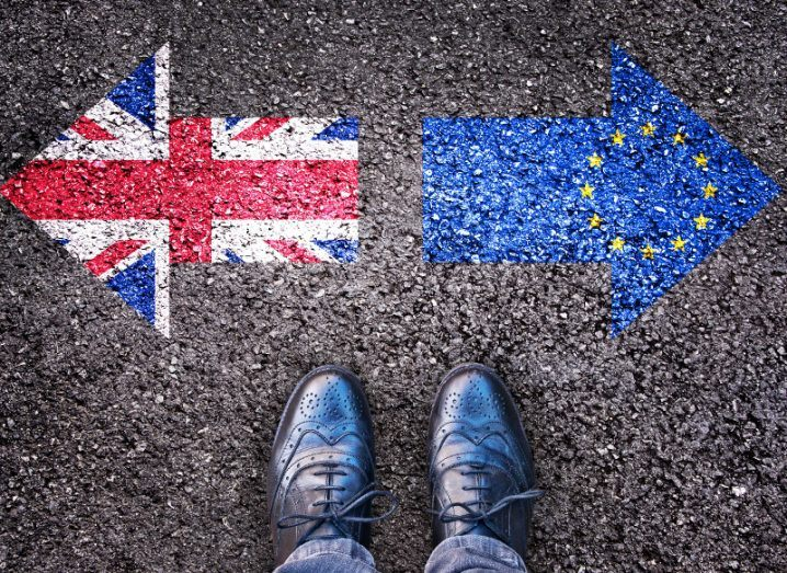 A pair of feet in black leather shoes standing in front of UK and EU flags painted on an asphalt surface.
