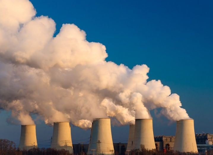 6 wide chimney towers emitting large amounts of CO2 against a blue sky background.