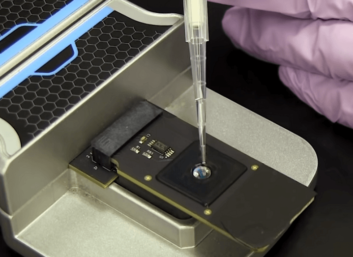 Close-up of a genetic sample being placed on a reader and inserted into the CRISPR-Chip device.