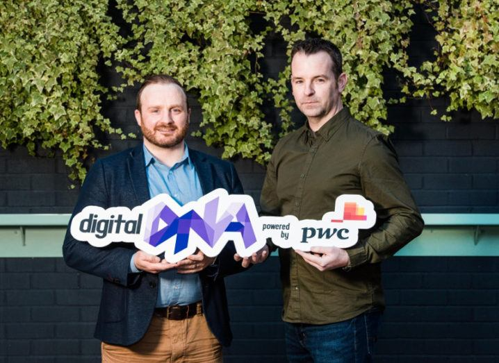 Two men in business-casual attire holding a sign for Digital DNA and PwC.