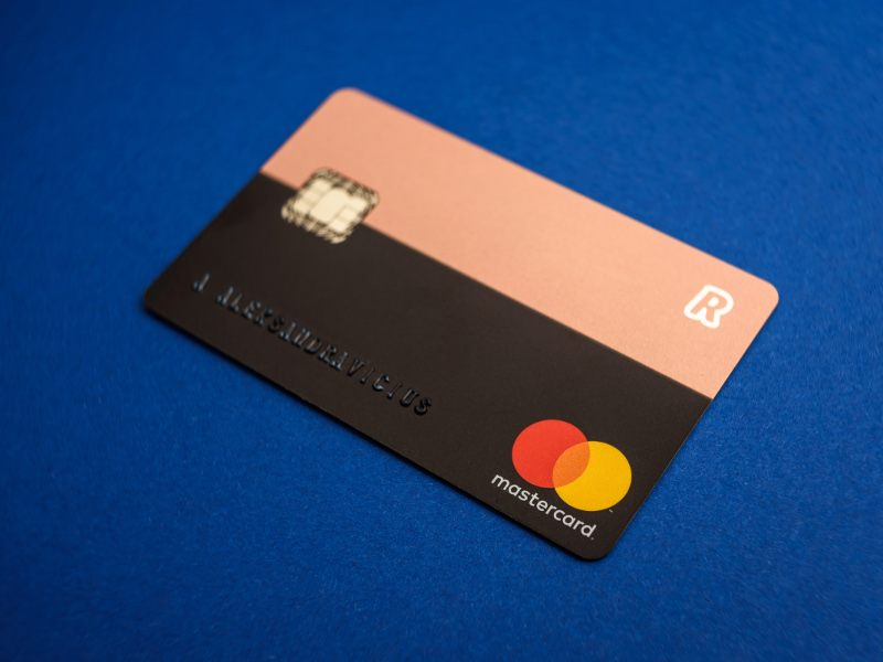 Close up view of a Revolut card issued by Mastercard against an electric blue background