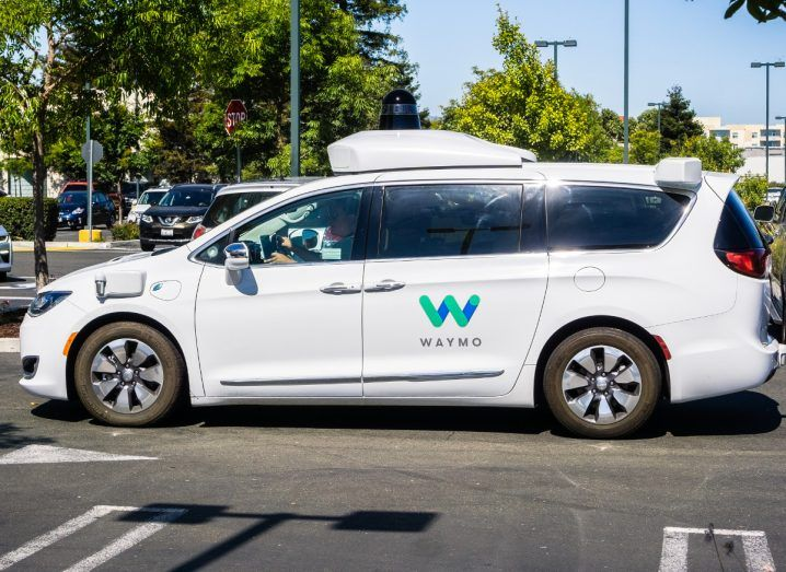 Close up of a white Waymo self-driving car outside on a bright day. The Waymo logo is on the side.