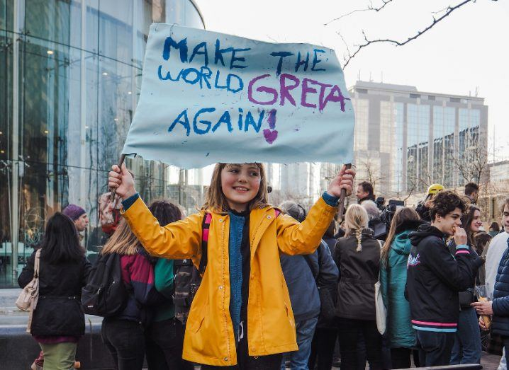 A young girl in a yellow raincoat stands on a bench amid a crowd of protesters holding up a sign that reads: 'Make the world Greta again!'