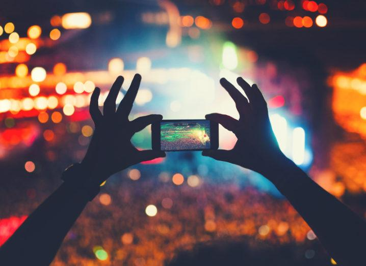 Silhouetted arms hold a smartphone up against a crowded concert lit with colourful lighting. The phone is capturing a video.