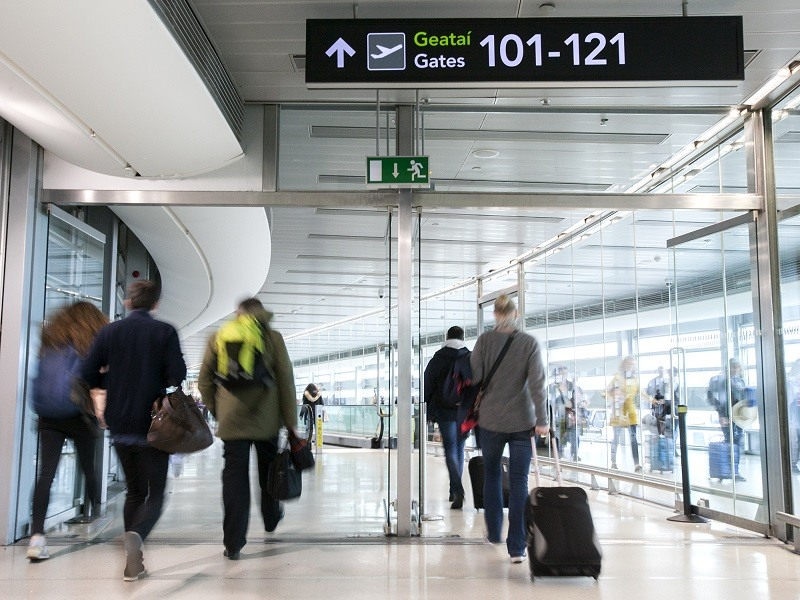 Passengers walking through Dublin Airport with luggage on their way to boarding gates.