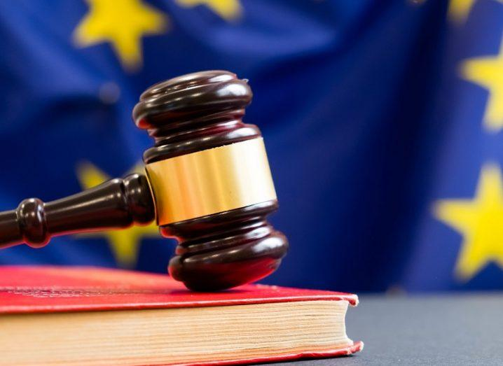 Gavel on top of a red book with an EU flag in the background.