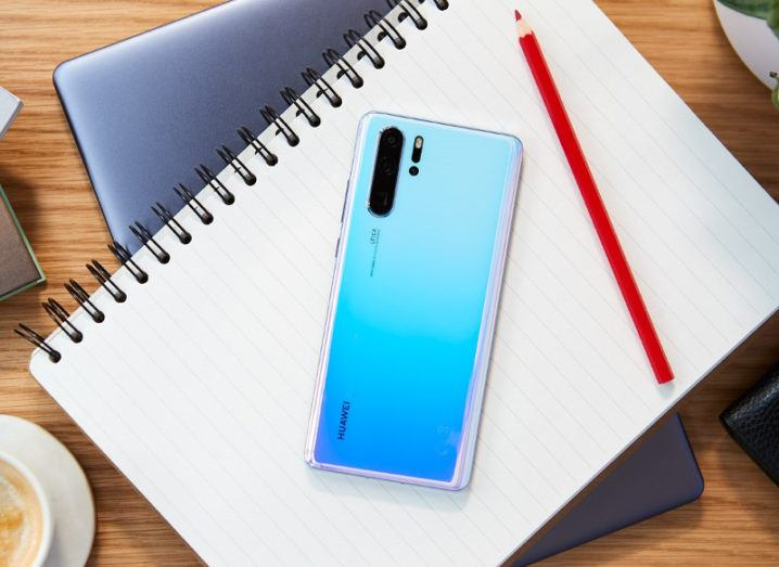 Picture of a blue-coloured Huawei P30 smartphone on a notebook beside a red pencil.
