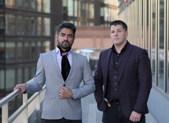 Two dapper men stand on the balcony of a building.