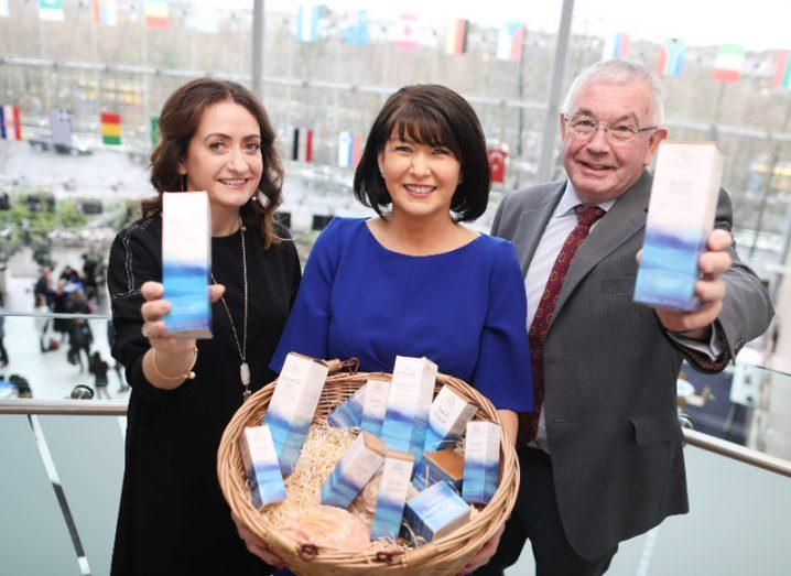 Woman in blue dress with black hair holds a basket of products while a man and woman either side of her hold the products in the air.