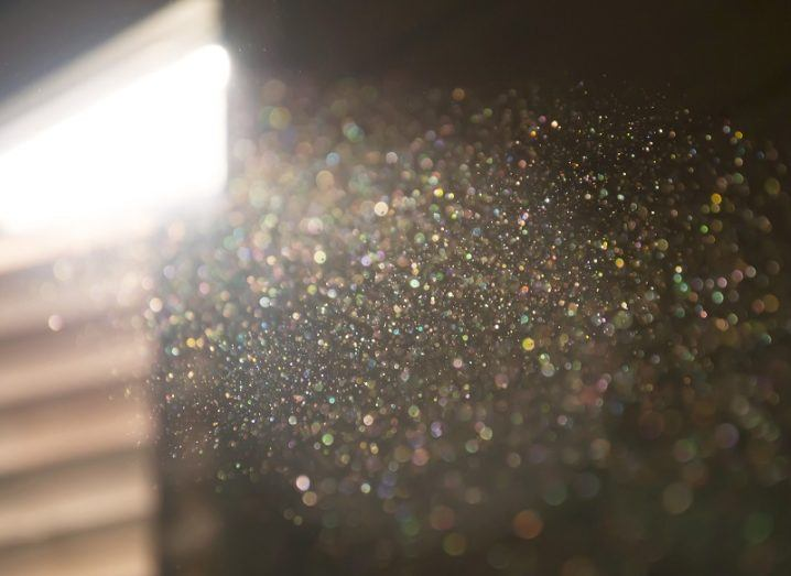 Close-up of household dust particles illuminated by sun beaming through a sliver of light from a window.