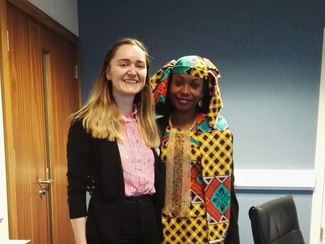 A woman in a colourful shirt and black blazer stands next to a woman in brightly patterned African robes and headdress.