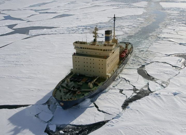 A large, beige icebreaker ship cutting its way through Arctic ice.