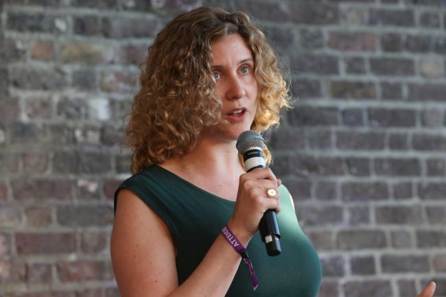 A woman with curly hair and a green top speaks into a microphone while standing in front of a brick wall.