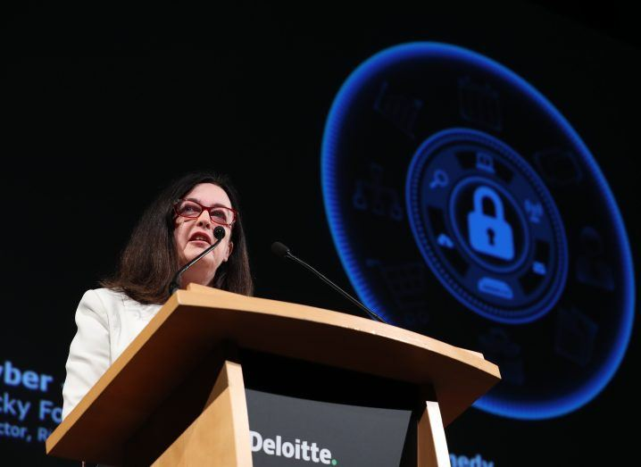 Woman with dark hair and glasses wearing a white jacket speaking from a podium.