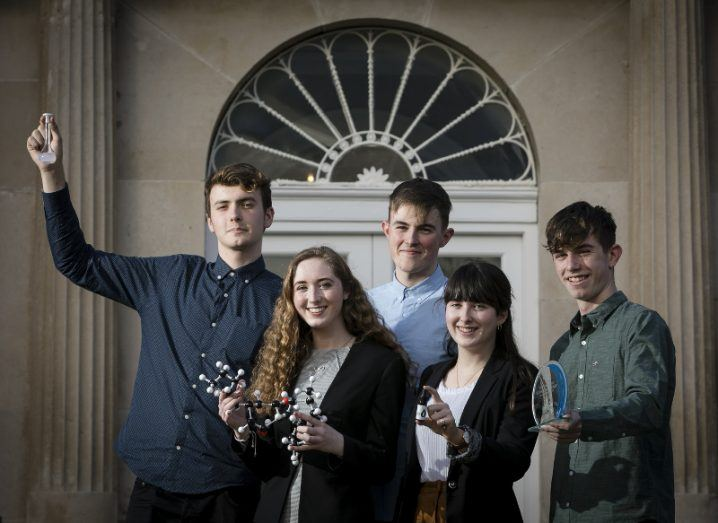 Three young men and two young women stand in a doorway holding scientific props and a glass award.