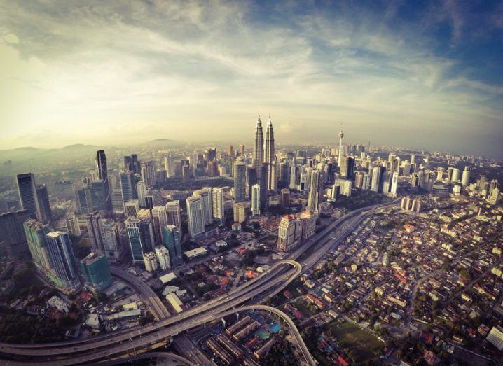 Aerial view of the Malaysian capital city of Kuala Lumpur with sun rising over a blue cloudy sky.