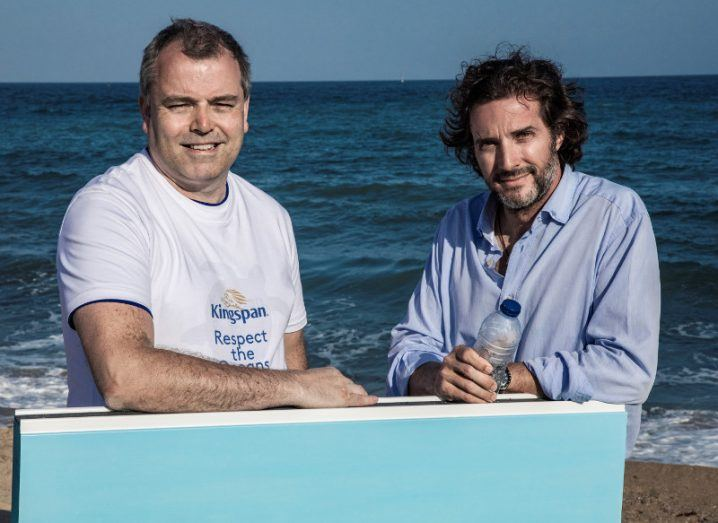 Two casually dressed men standing by the sea with one holding a plastic bottle, symbolising recycling.