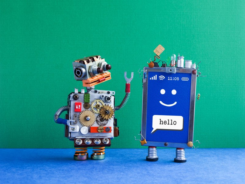 Two robots greet each other while one says hello and salutes with a SIM card for a hat against bright green background.