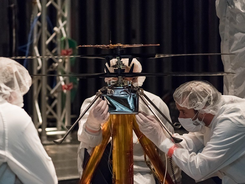NASA researchers in white overalls tinkering with the small Mars Helicopter.