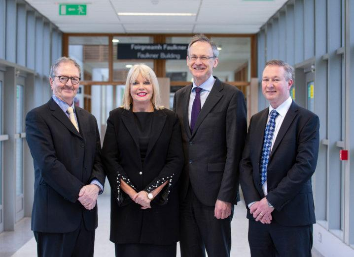 Three men in suits and one blonde woman in business dress standing in Dundalk IT and smiling.