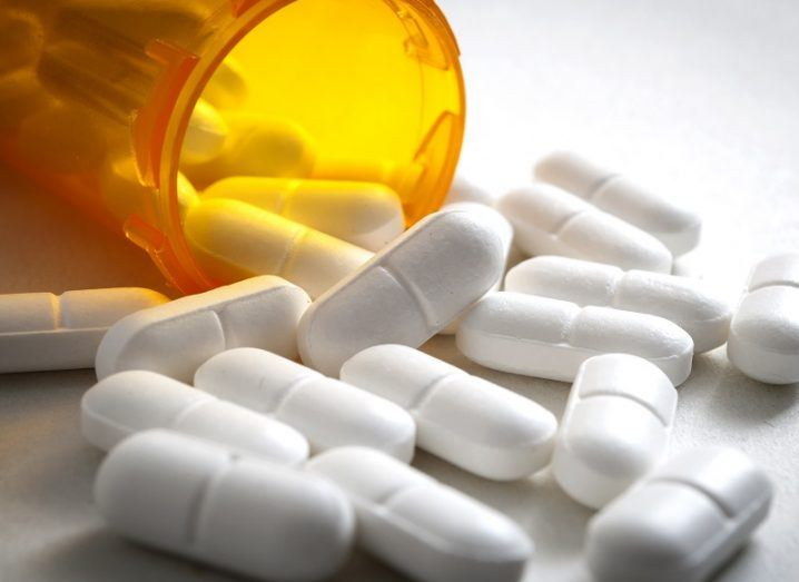 Painkiller pills flowing out of an amber plastic container.