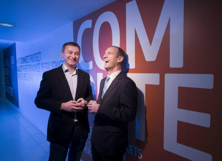 Two men in suits in a data centre in front of an orange wall with one of them laughing.