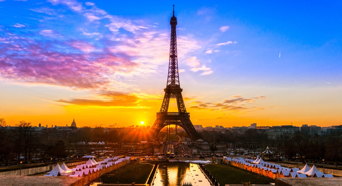 A vibrant sunset in Paris. The Eiffel Tower is in the centre and the sky is deep blue, descending into bright orange.