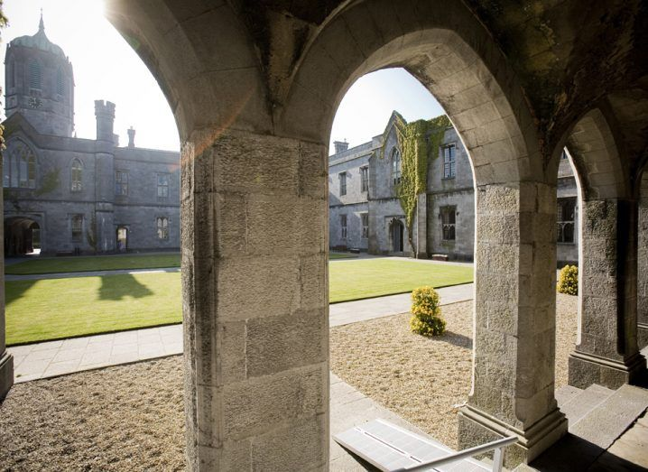Arches around a green square in a university. It is the quadrangle of NUI Galway.