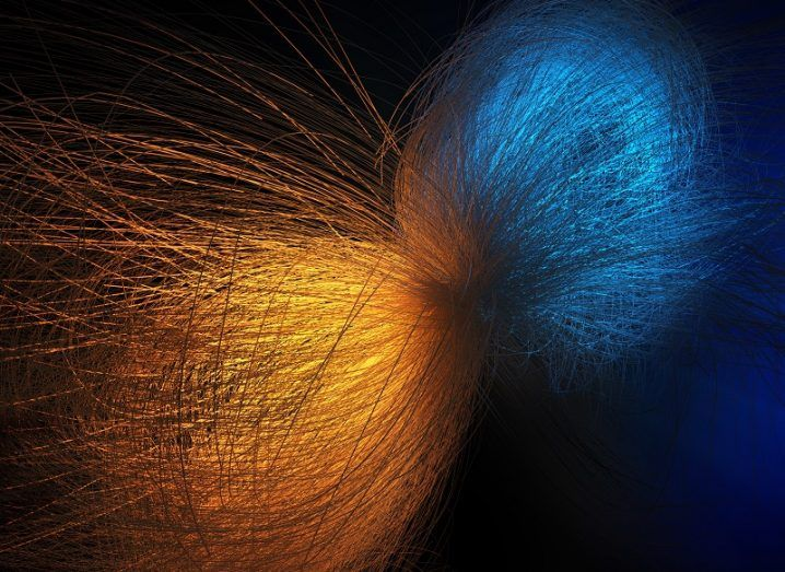 Abstract of two particles - one orange and one blue - colliding against a black background.