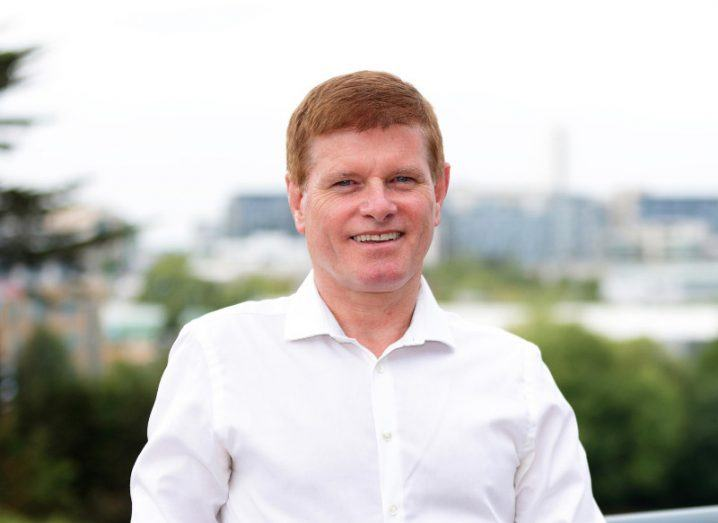 red-haired man in white shirt standing outside with greenery in the background.