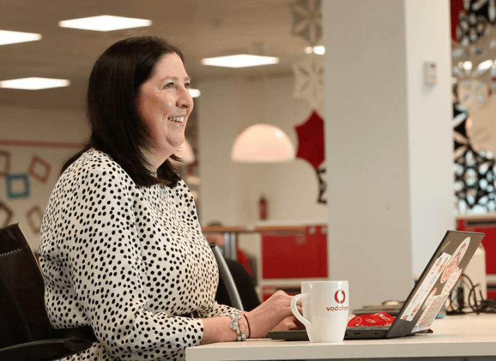 A woman in a polkadot dress smiles as she looks up from her laptop, which is next to a Vodafone mug.