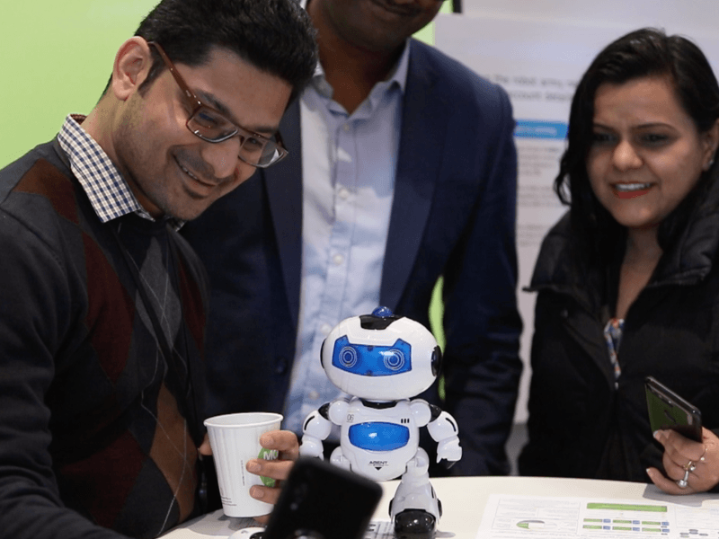 A man holding a coffee cup gets a selfie with a small robot toy while two people wait in the background to take a selfie of their own.