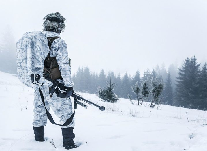 Soldier in winter camouflage holding a rifle looking out over a forest area.