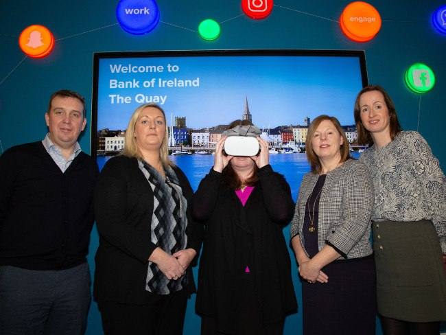 A man and four women, one of them wearing a VR headset.