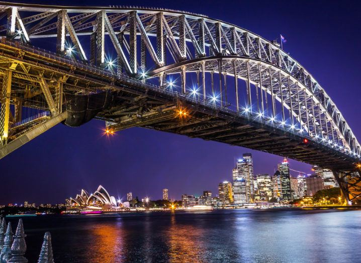 A view of the city of Sydney from under the Harbour Bridge at night time.